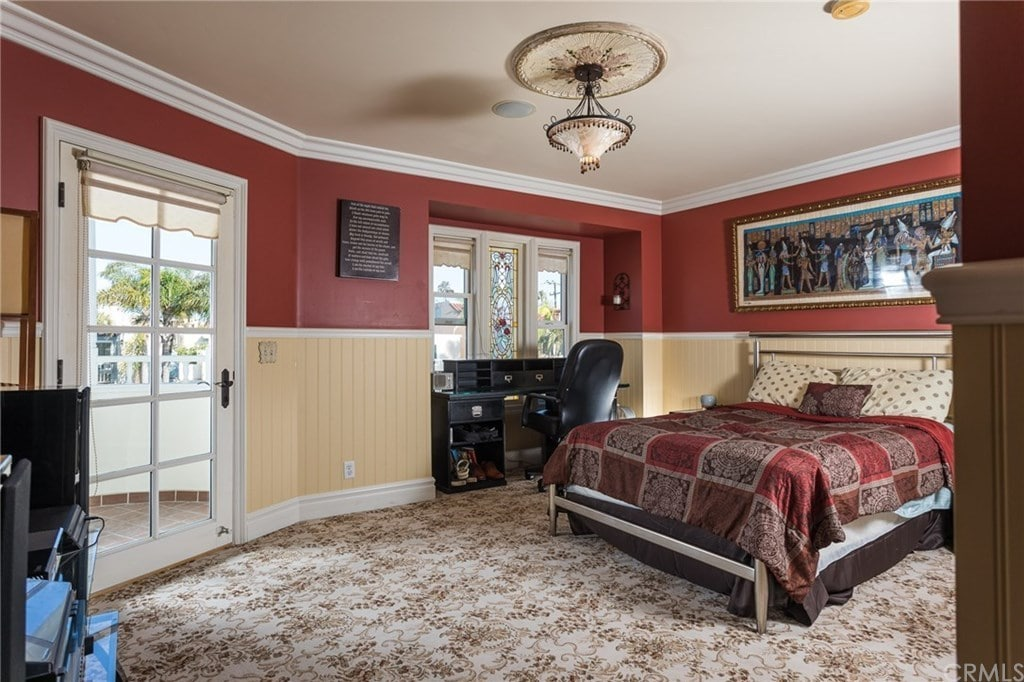 Victorian primary bedroom decorated with a charming pendant light and a rectangular artwork mounted above the beige beadboard wall. It showcases a chrome metal bed with a black desk on the side over the floral carpet flooring.