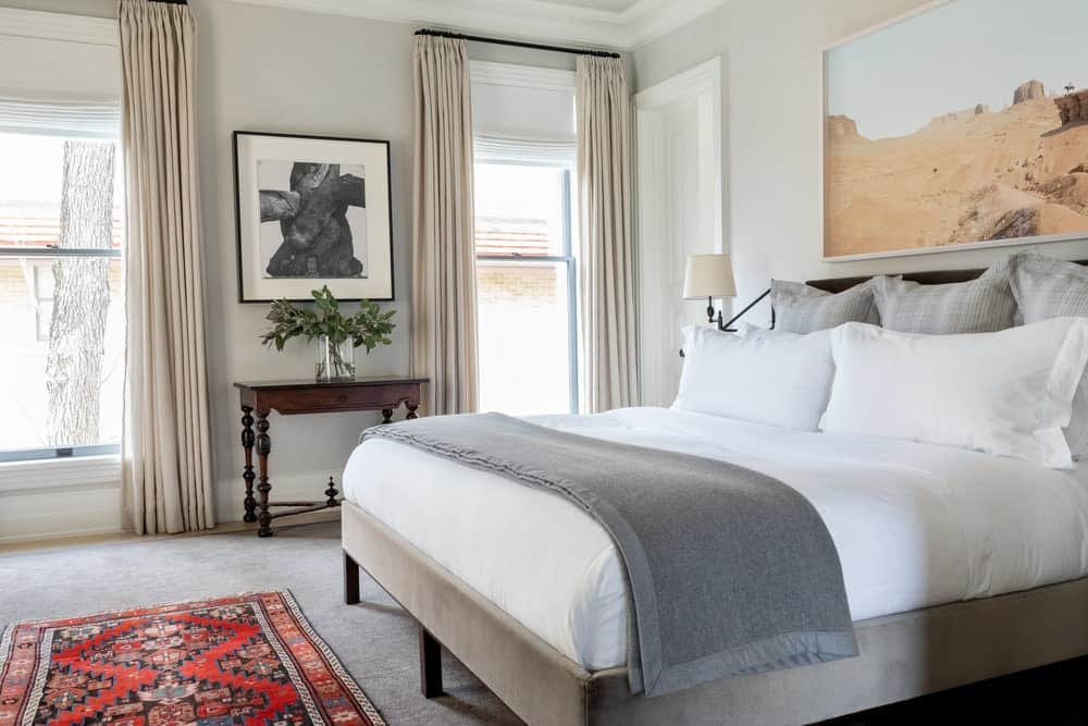 A closer look at this primary bedroom featuring a gray upholstered bed complemented by a red patterned rug over carpet flooring. An abundance of natural light flows in through the glazed windows that are covered in sheer drapes.
