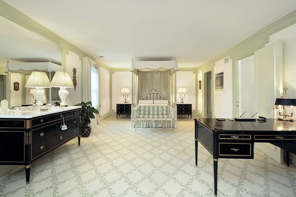 The spacious flooring is covered with a white carpet that has charming leafy patterns. This matches with the hues of the bed frame, headboard and decorative curtains. These light hues contrast the black bedside drawers, dresser and desk.