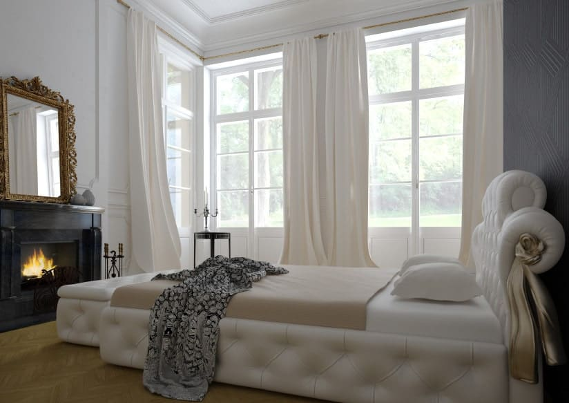 The majestic white bed has a white leather tufted frame and headboard matching with the cushioned foot locker at the foot of the bed near the fireplace that is inlaid with contrasting black wood for its mantle making its stand out against the white walls.