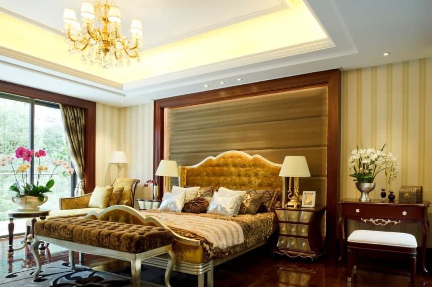 The white tray ceiling is dominated by a brilliant golden chandelier that matches the hue of the velvet tufted headboard of the traditional bed. This golden hue makes it glow against the dark wooden flooring that extends to the wall panel and the bedside table.