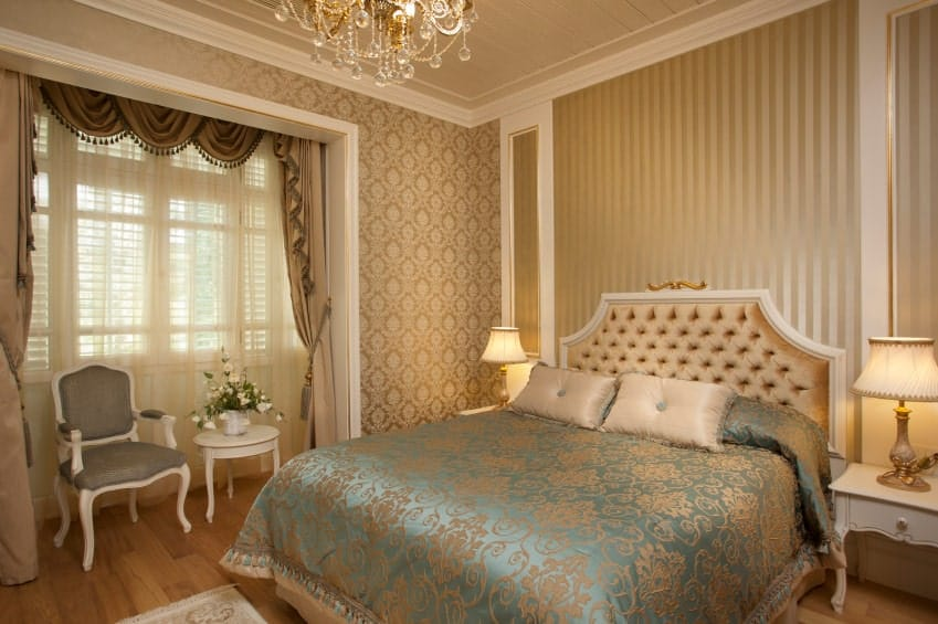 The brilliant blue comforter of the Victorian-style bed has subtle elegant pink patterns on it that complements the pink patterned wallpaper of the walls as well as the beautiful tufted headboard that is brightened with the warm yellow lights of the table lamps.