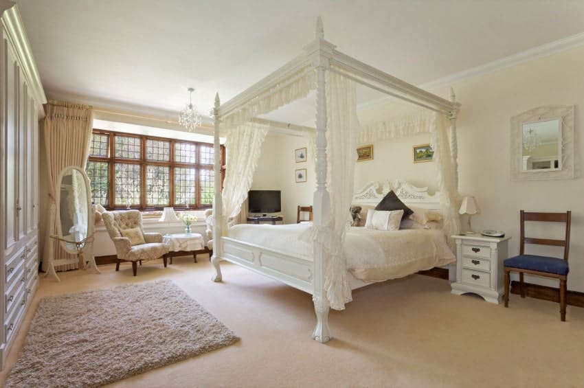 The white wooden four-poster bed has light pink sheets that match the carpeted flooring that goes well with the white wall behind the bed and the white built-in cabinet on the other side by the furry area rug adjacent to the sitting area.