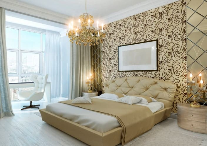 The majestic and elegant golden chandelier that hangs from the white ceiling matches with the two table lamps that are flanking the low platform bed with a golden hue to its frame and tufted headboard. This is accented by a large wall dominated by a wallpaper with intricate patterns on it.