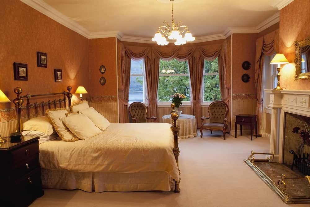 The traditional bed has a metal frame and headboard with a golden hue to it that matches with the simple chandelier with a flower design and the table lamps placed on the bedside drawers and the white mantle of the fireplace by the foot of the bed.