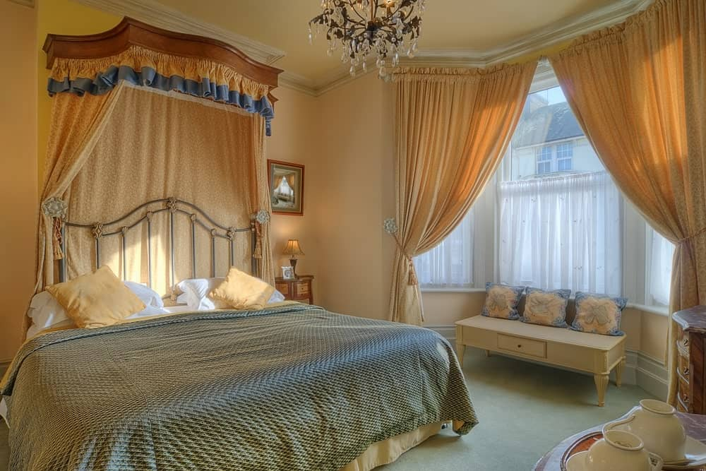 The light pink ceiling is adorned with a peculiar decorative chandelier that looks like a dandelion. This goes well with the metal railing headboard of the traditional bed that has a decorative curtain in the same hue as the pink window curtains.