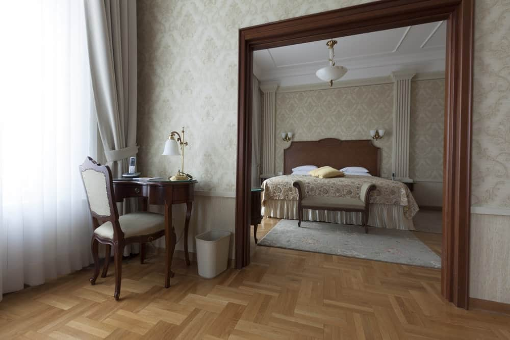 The entryway to this Victorian-style bedroom has dark brown wooden molding on its edges that contrast the light gray patterned wallpaper of the walls. This serves as a nice background for the dark wooden headboard of the bed that is topped with a couple of wall-mounted lamps.