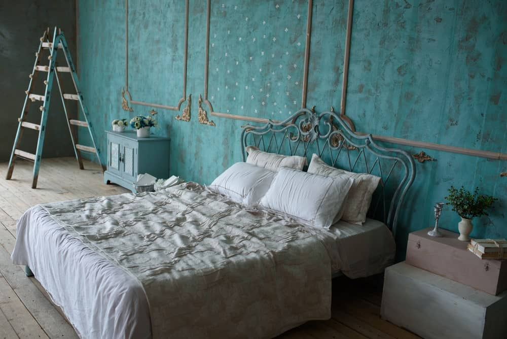 This room is a wonderful fusion between the Victorian-style elements and the rustic elements of the distressed wooden flooring and the shabby chic green walls with decorative smears on it. This is paired with white bed sheets and wooden boxes for a bedside table.