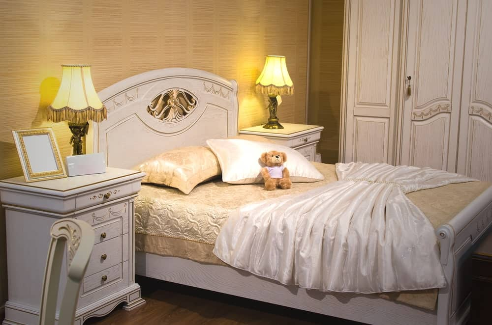 This simple Victorian-style kid's bedroom has a light gray sleigh bed that matches with the elegant bedside drawers and the large cabinet on the side. The bed has beige sheets and pillows that blend with the wallpaper augmented by the warm yellow lights of the table lamps.
