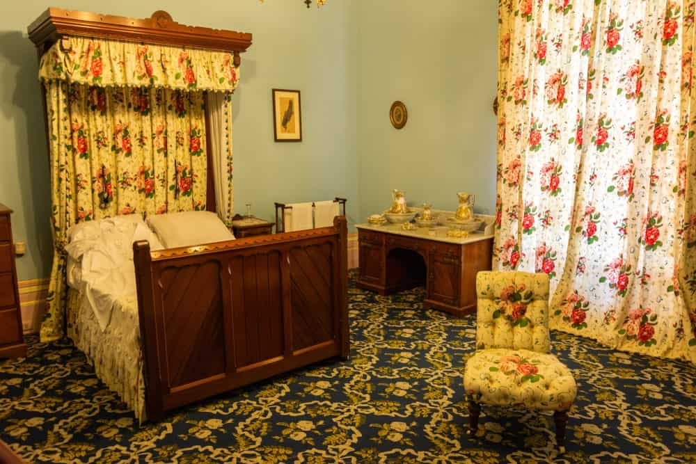 The green patterned carpeting of the floor together with the floral curtains of the window and bed provide a complex background of patterns and contrasting colors for the simple wooden bed and light green walls with wall-mounted artworks.