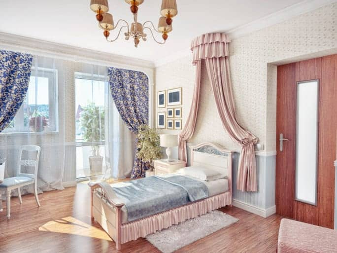 This is a lovely girl's bedroom in an elegant Victorian-style setup. There is a decorative pink curtain above the wooden headboard that matches with the side skirts of the bed frame. This is paired with a patterned wallpaper and a hardwood flooring.