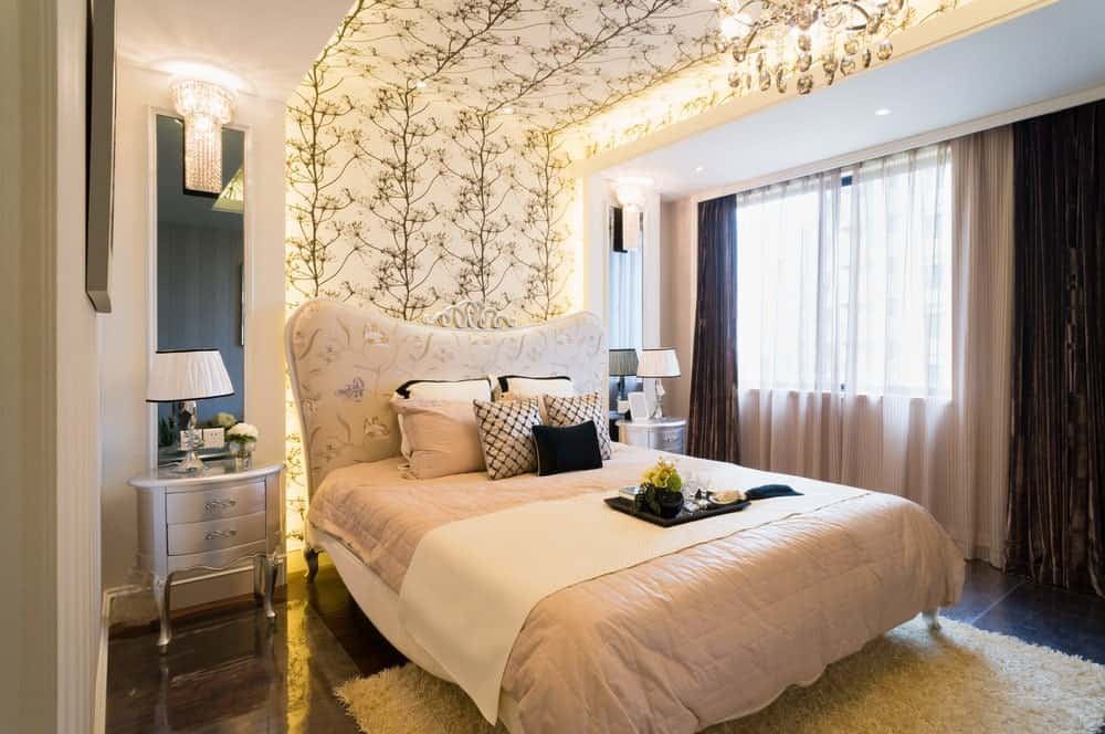 The charming chic pink bed with a floral cushioned headboard is against a lit portion of the light pink wall that has a wallpaper of flowering branches. This extends to the ceiling above the pink sheets of the bed that is flanked with silver bedside drawers.