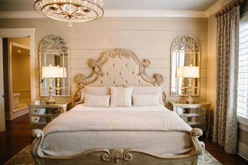 The two bedside drawers flanking the sleigh bed has a mirrored facade that matches with the wall-mounted mirrors above them. These mirrors stand out against the beige shiplap wall augmented by the warm yellow lights of the table lamps.