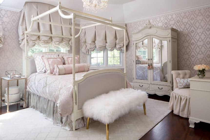 The charming white wooden four-poster bed of this Victorian-style bedroom is dominated by the light gray elements of the bed sheets, wallpaper and curtains. The bench at the foot of the bed has a white furry cushion and golden legs that stand out against the white patterned area rug.