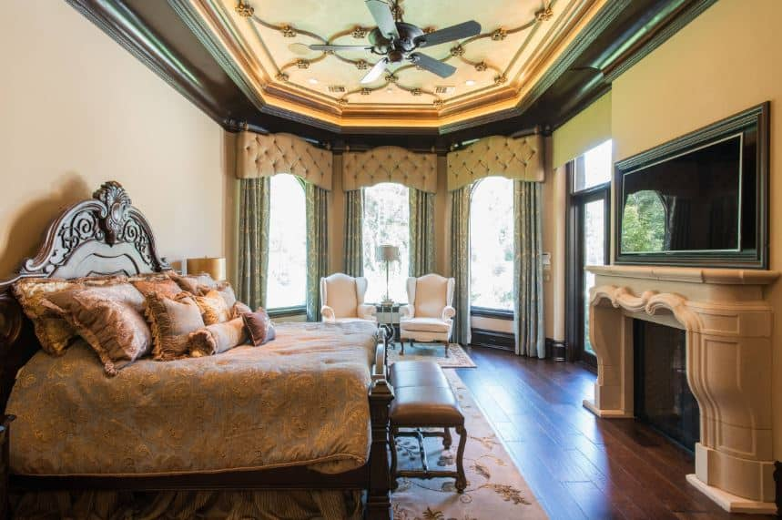 The beige mantle of the fireplace supports the TV across from the dark wooden sleigh bed with an elegant wooden headboard filled with carvings. This headboard contrasts the beige wall but matches with the ceiling and hardwood flooring.