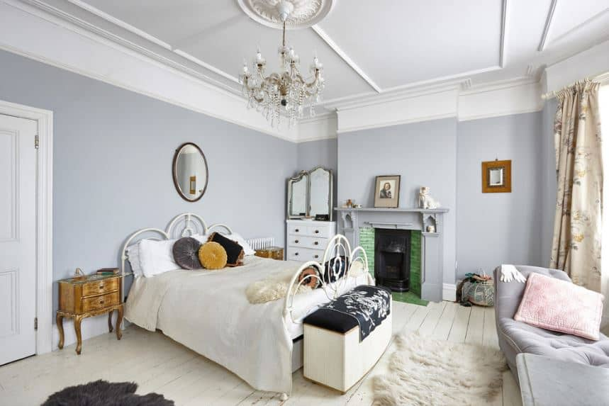 The light gray walls that go well with the white ceiling is accented with a fireplace by the side of the white wrought iron bed with matching white sheets. This is a nice complement to the white shiplap flooring illuminated by the brilliant windows by the foot of the bed.