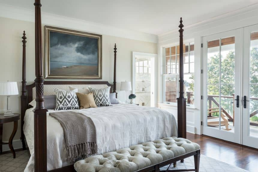 The dark brown pencil poster bed is the highlight of this Victorian-style primary bedroom with simple light beige walls and white ceiling. The light beige wall behind the cushioned headboard is accented with a beautiful painting of a cloudy beach.