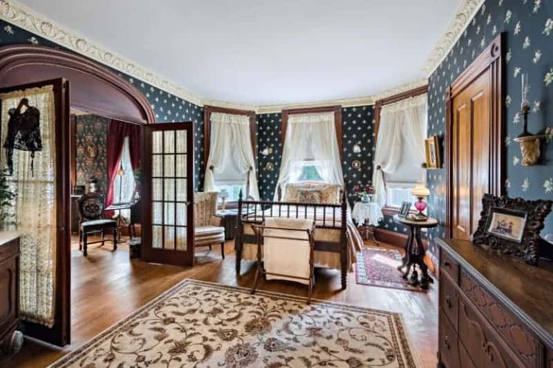This gorgeous bedroom has a four-poster bed surrounded by curtained windows that brighten up the dark patterned wallpaper that dominates the walls. This also complements the wooden elements of the cabinets and hardwood flooring with floral area rug.