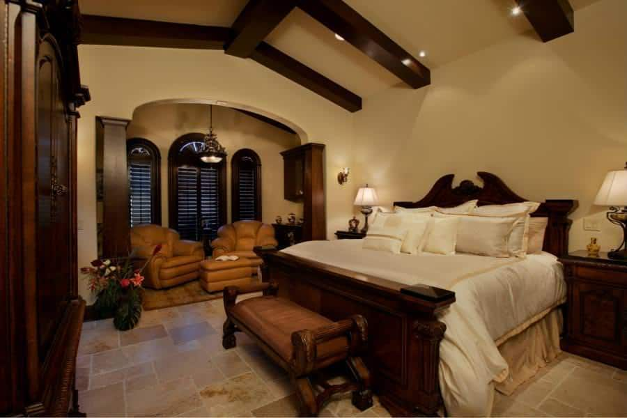 This gorgeous primary bedroom has elegant beige walls and cathedral ceiling that are complemented by the dark wooden exposed beams that match with the large wooden sleigh bed and the arched shuttered windows on the far end by the sitting area.