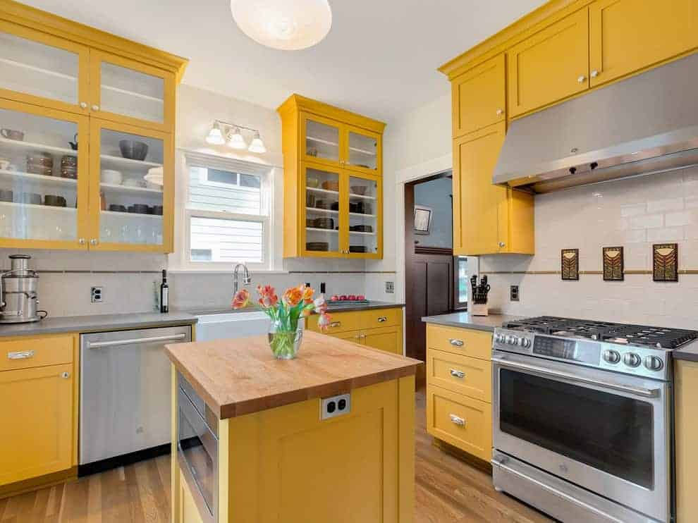 This kitchen offers yellow and glass front cabinets along with a small island that's topped with a wooden counter. It has natural hardwood flooring and a white framed window with wall sconces on top.
