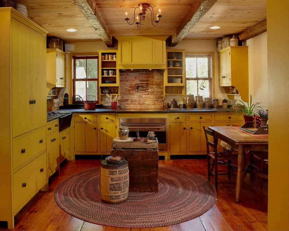 Cozy eat-in kitchen with wide plank flooring and wood-paneled ceiling mounted with recessed lights and a candle chandelier. It includes yellow cabinetry and wooden dining set next to the multi-colored round rug.