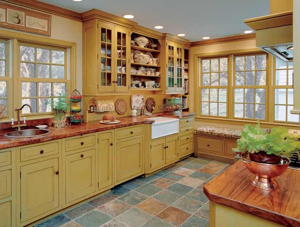 Farmhouse kitchen with limestone flooring and framed windows overlooking the outdoor scenery. It includes yellow and glass front cabinets along with a seat nook that's topped with a floral cushion.
