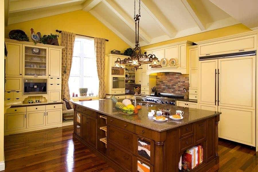 Classic kitchen with light yellow cabinetry and an immense central island topped with a granite counter. It is illuminated by a vintage chandelier that hung from the cathedral ceiling lined with white beams.