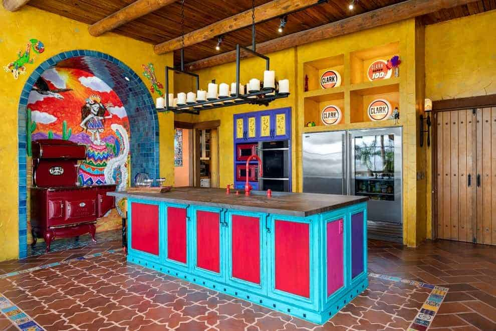Southwestern kitchen offers stainless steel appliances and a blue island bar accented with red doors and fixtures. It has terracotta flooring and wood beam ceiling mounted with track lights and a linear chandelier.