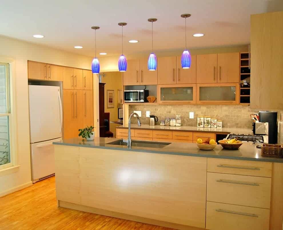 Modern kitchen with a white fridge and light wood cabinetry complementing with the peninsula that's fitted with an undermount sink and gooseneck faucet. It is illuminated by blue pendants and recessed ceiling lights.