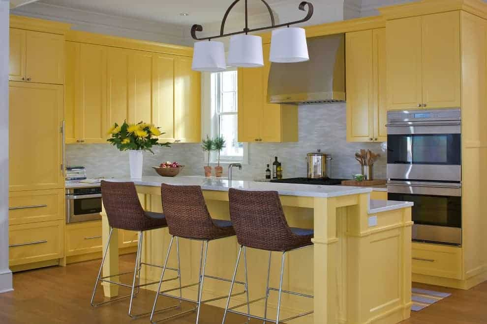 Wicker counter chairs sit at a two-tier island bar topped with quartz counters. It is accompanied by white drum pendant lights and yellow cabinetry against the stone tile backsplash.