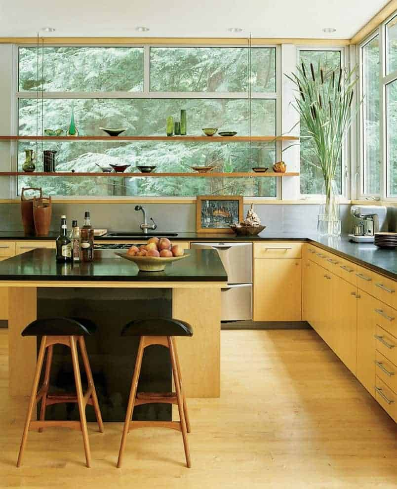 Fresh kitchen features light wood cabinets and a matching breakfast island blending in with the hardwood flooring. It has black countertops and floating shelves against the glass-paneled windows overlooking the enchanting forest.