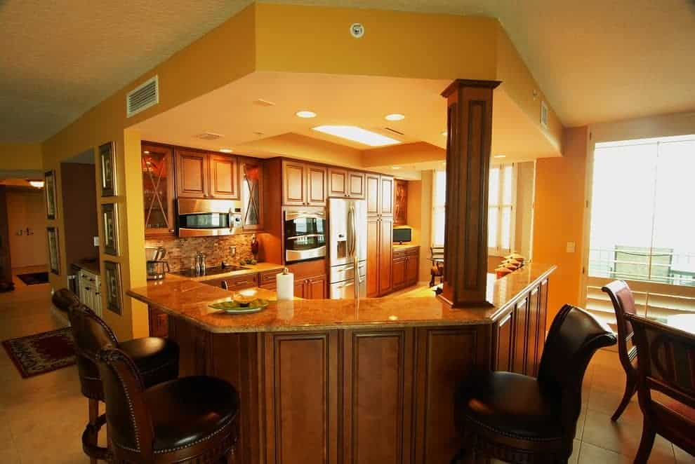 Traditional kitchen enclosed in a curved bar that's lined with a wooden column. It showcases stainless steel appliances and natural wood cabinetry illuminated by recessed ceiling lights.