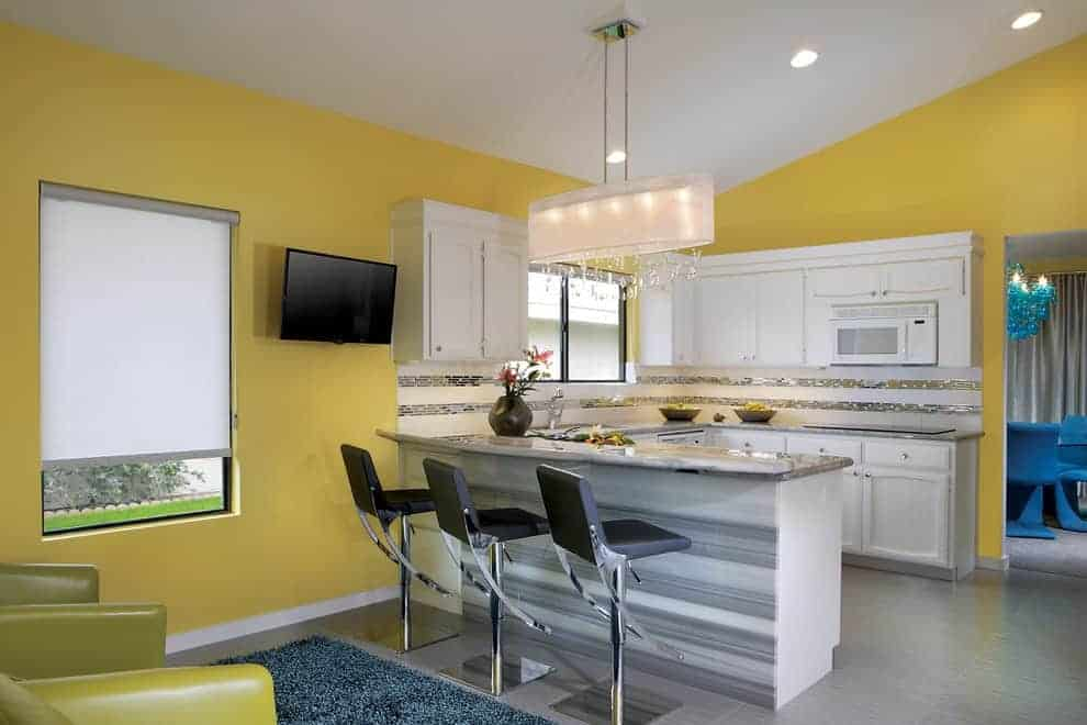 Yellow kitchen with granite top peninsula paired with black counter stools and lighted by a crystal chandelier along with white cabinetry and backsplash that's accented with silver mosaic tiles.