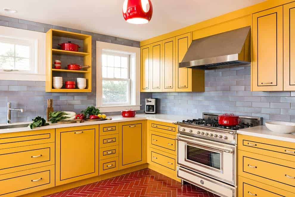 A red lighting fixture illuminates this kitchen featuring gray subway tile backsplash and yellow cabinetry highlighted by black trims. It has white framed windows and tiled flooring arranged in a herringbone pattern.