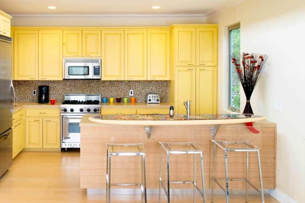 This kitchen showcases stainless steel appliances and yellow cabinetry accented with pebble backsplash. It includes a light wood peninsula with a raised eating counter lined with glass bar chairs.