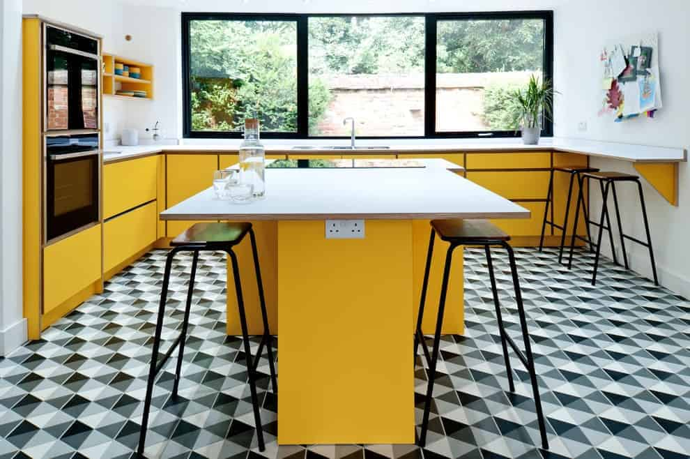 A black patterned flooring sets a striking backdrop to the sleek island bar paired with metal bar stools. It is accompanied by a double wall oven and yellow cabinets against the white walls.