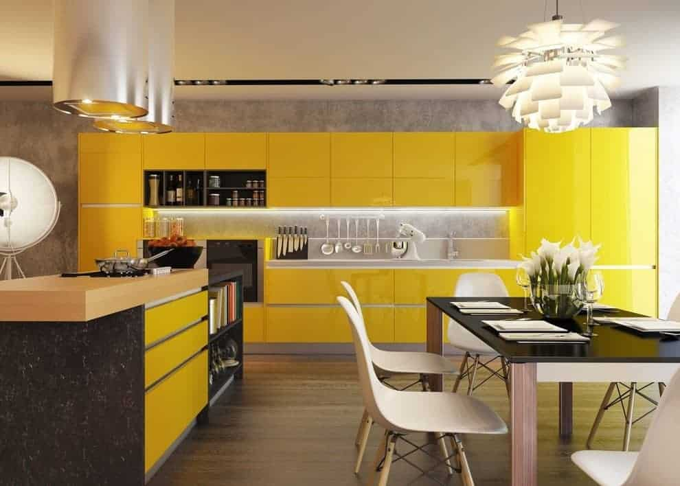 Contemporary kitchen with sleek yellow cabinetry and a wooden top island under cylindrical vent hoods. There's a modern dining set on the side lighted by a gorgeous chandelier.
