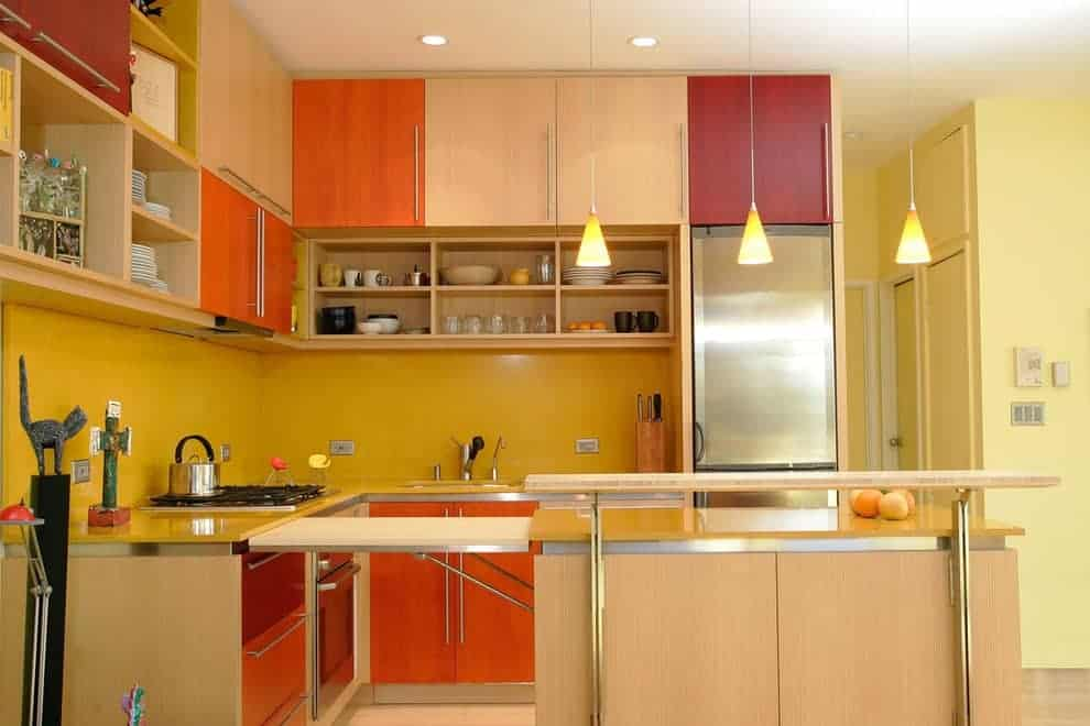 Yellow kitchen with multi-colored cabinets and a light wood breakfast bar topped with a raised counter. It is illuminated by warm cone pendants and recessed ceiling lights.