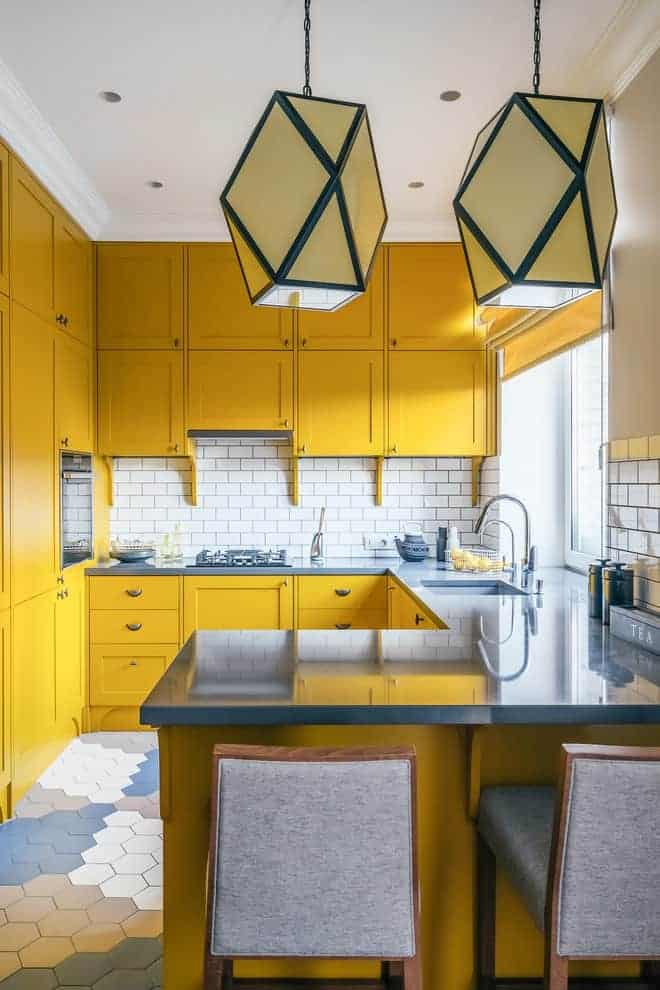 Contemporary kitchen showcases black appliances and yellow cabinetry against the white subway tile backsplash. It includes a small peninsula over multi-color hex tiled flooring with gray counter chairs illuminated by large geometric pendants.
