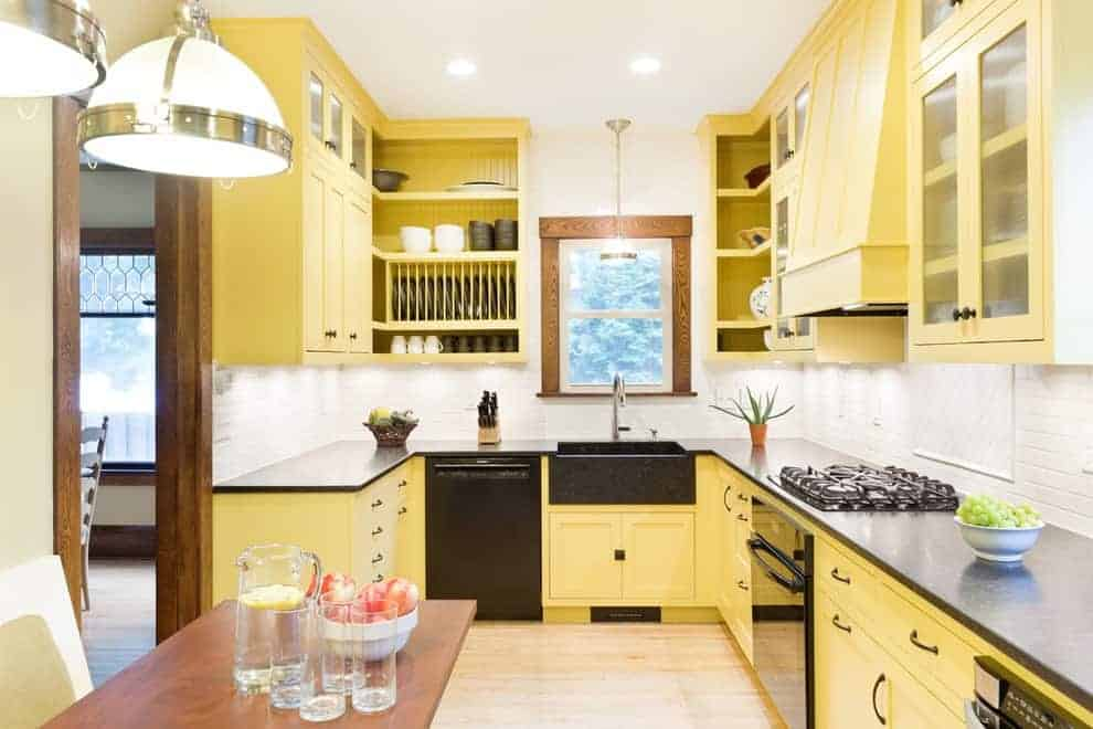 An eat-in kitchen with yellow cabinetry and black appliances complementing with the farmhouse sink that's paired with a gooseneck faucet. It includes a wooden dining set lighted by glass dome pendants.