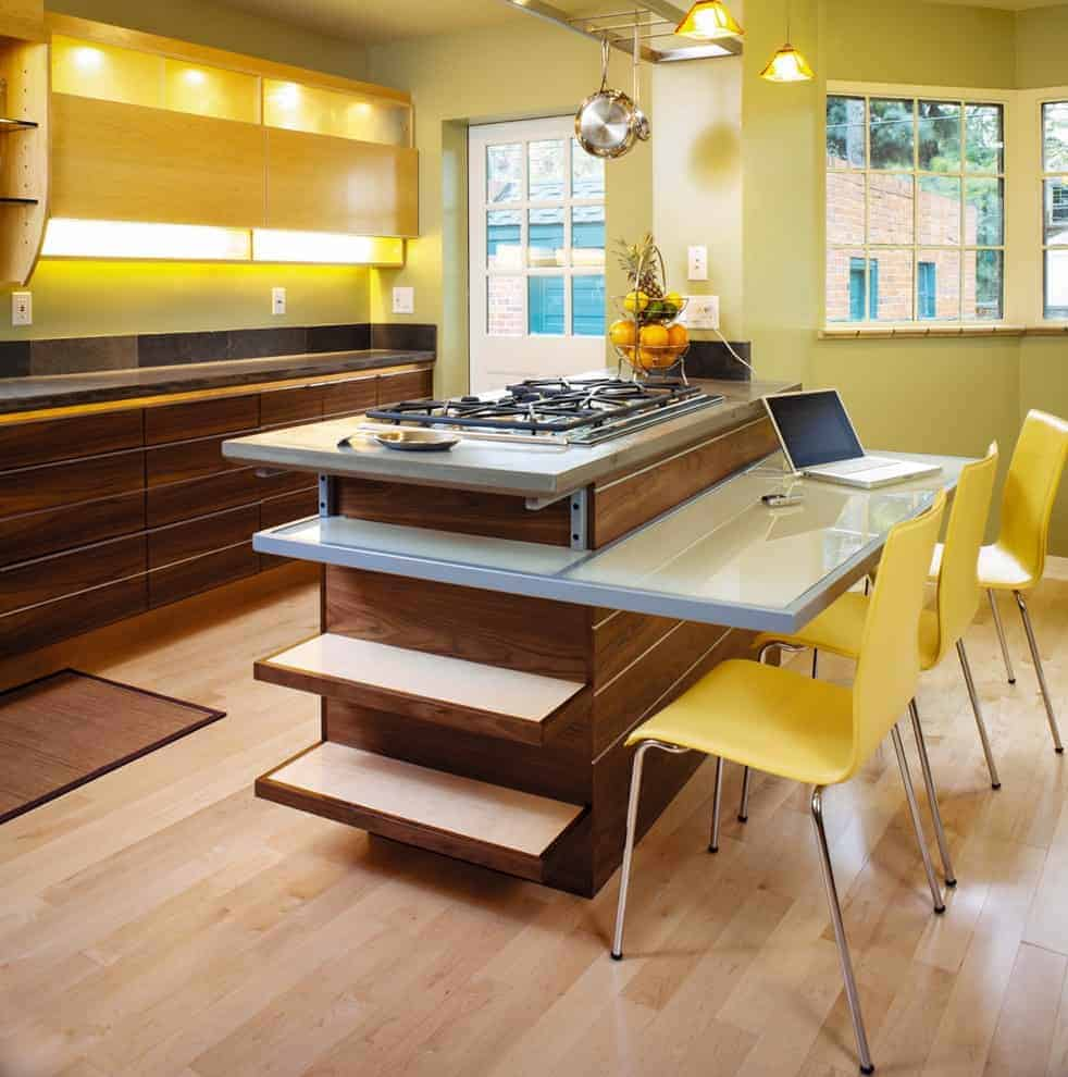 Stainless steel pot rack and warm dome pendants hang over the dark wood kitchen bar that's integrated with an eating counter and open shelving. It is accompanied by wooden cabinets and sleek yellow chairs on light hardwood flooring.