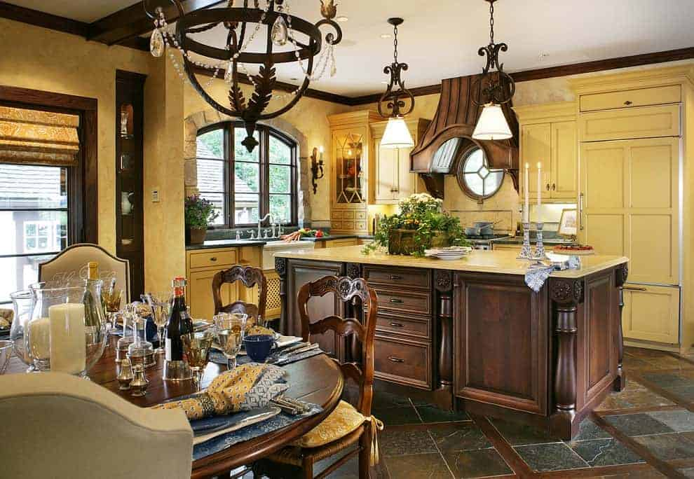 Yellow cabinetry provides a sleek contrast to the dark wood kitchen island and vent hood that's fixed above a circular window. This kitchen is illuminated by a fabulous chandelier and a pair of glass dome pendant lights.
