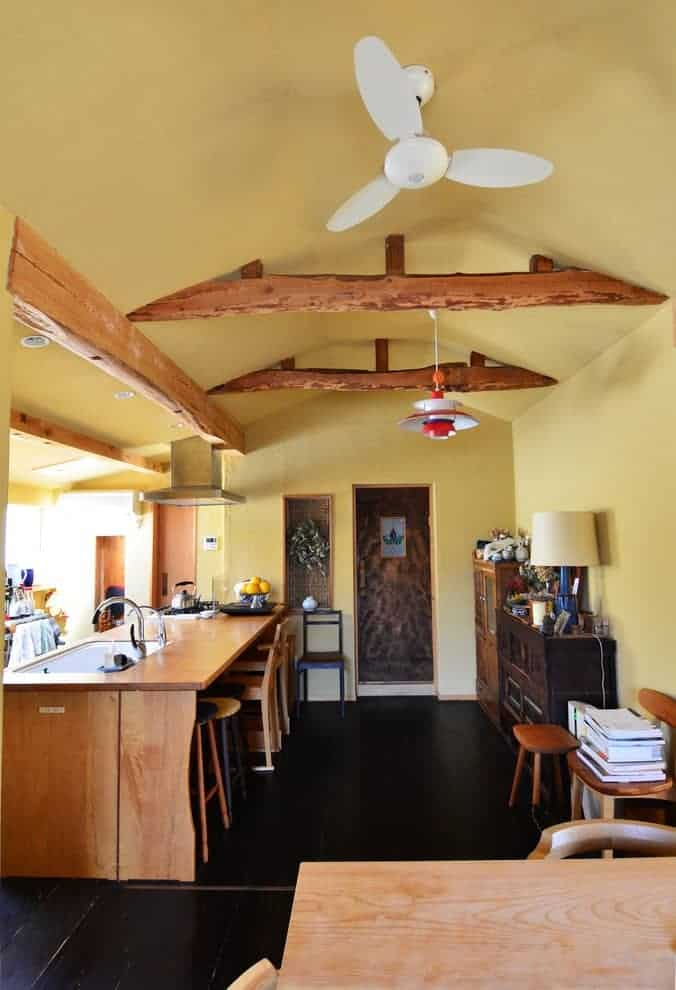 Asian kitchen with black tiled flooring and yellow vaulted ceiling lined with rustic beams. It includes wooden cabinets and a breakfast bar fitted a porcelain sink and chrome fixtures.