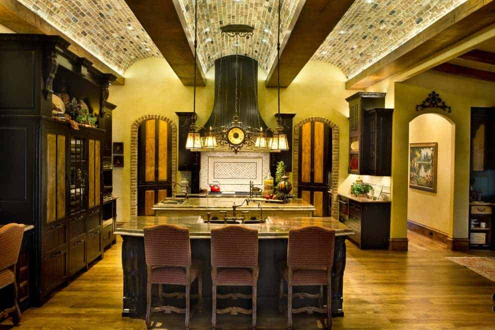 Ambient light from the vintage chandelier creates a warm and cozy feel in this kitchen with dual island bars and dark wood cabinetry against the yellow walls. It has hardwood flooring and a stunning barrel-vaulted ceiling clad in bricks.