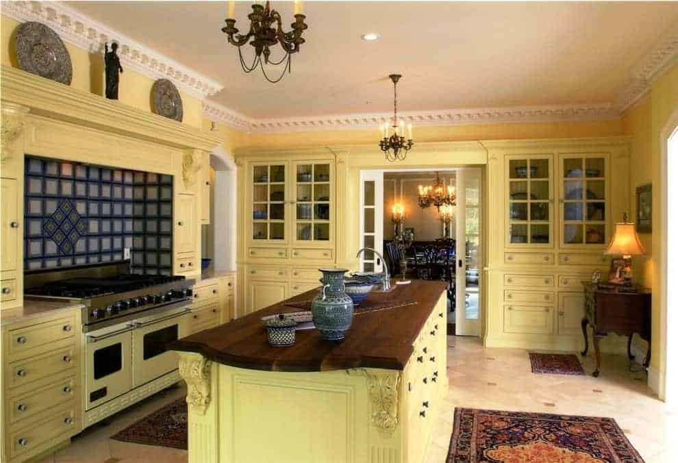 A pair of candle chandeliers hang over the kitchen island topped with a dark wood counter and an undermount sink. It is surrounded by light yellow cabinetry and a cooking alcove designed with decorative plates and antique sculpture.