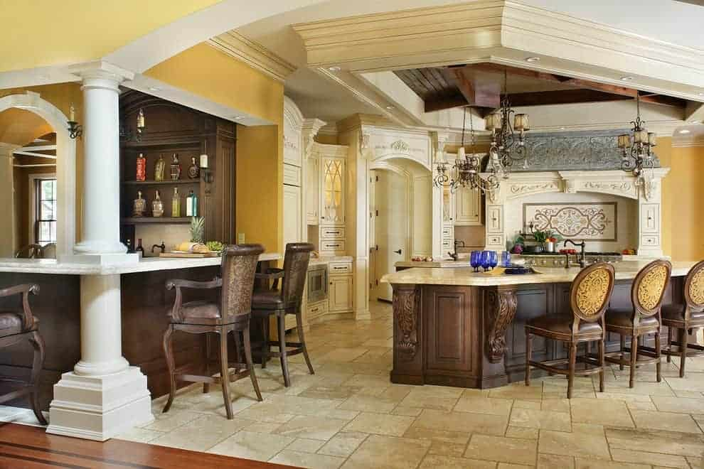 The luxury kitchen offers a bar and granite top island lined with round back chairs over limestone flooring. It includes an ornate cooking alcove and vintage chandeliers that hung from the tray ceiling.