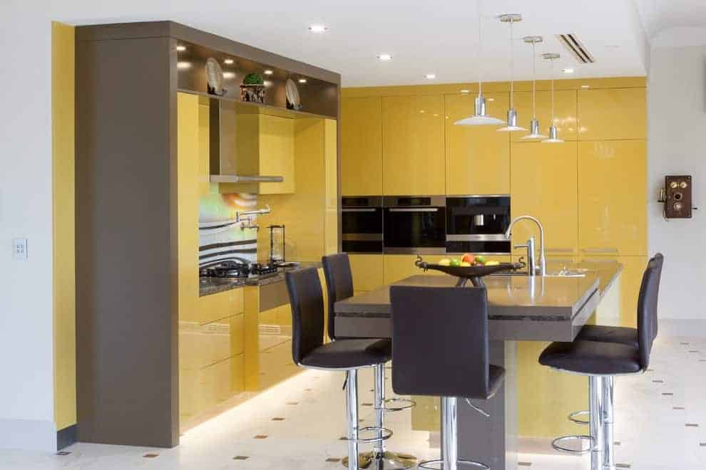Modern kitchen with yellow high gloss cabinetry and a sleek breakfast bar paired with black leather chairs. It is illuminated by chrome dome pendants and recessed ceiling lights.