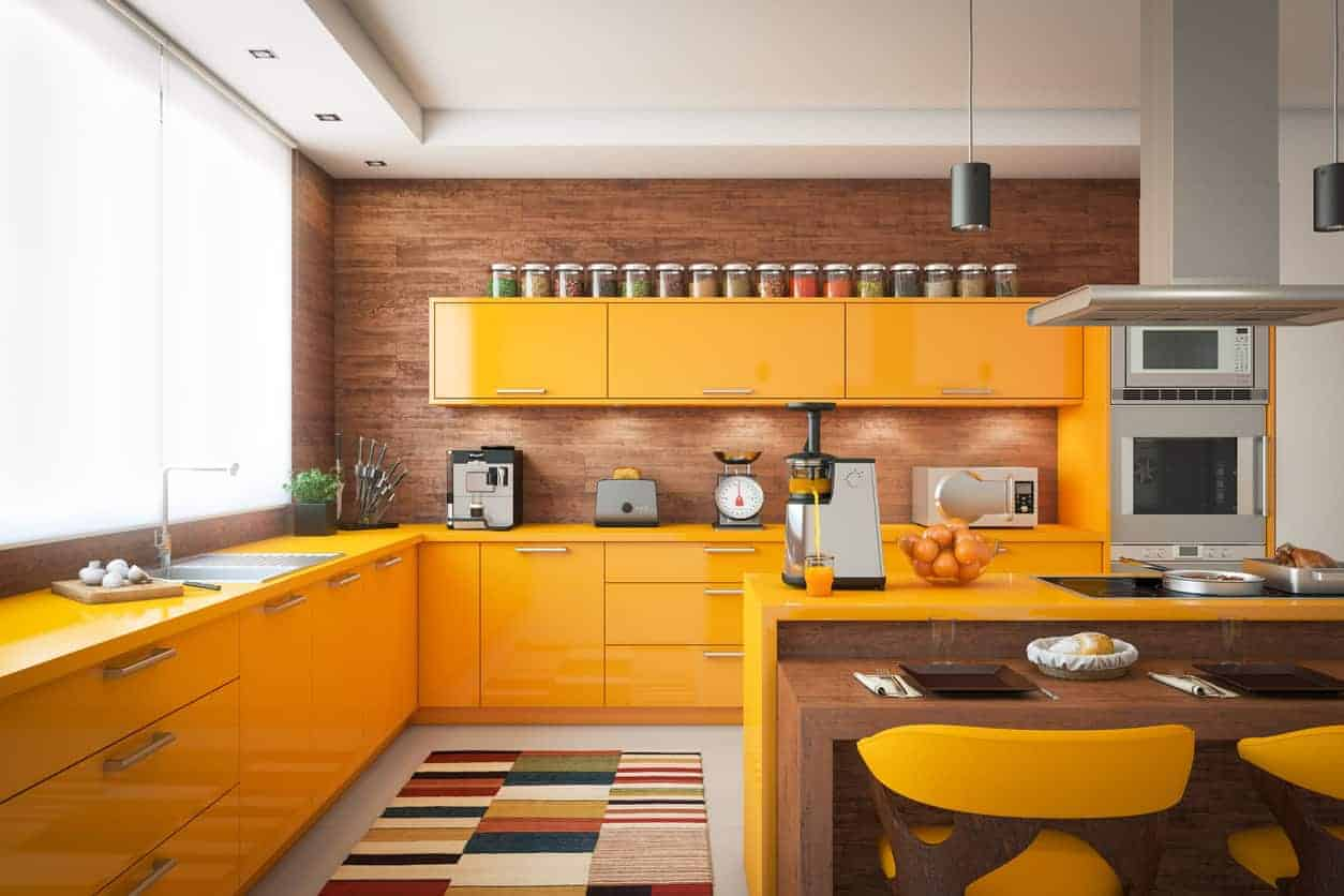 A sleek range hood is suspended over a two-tier island bar illuminated by gray pendant lights. It is accompanied by yellow cabinetry and a multi-colored rug that lays on the white floor.