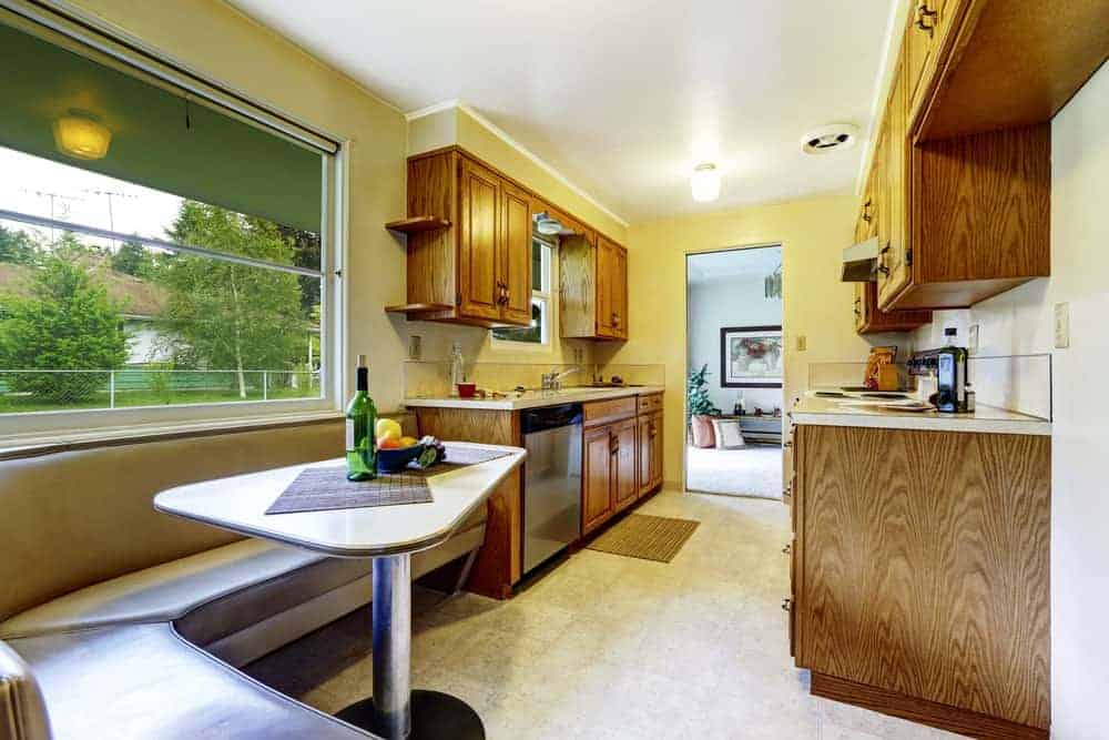 Yellow kitchen with tiled flooring and a glazed window overlooking the serene outdoor view. It includes wooden cabinetry and a breakfast nook completed with a metal table and a curved leather seat.