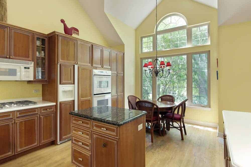 An eat-in kitchen with white appliances and wooden cabinetry matching with the granite top island that faces the round dining set lighted by a wrought iron chandelier. It has hardwood flooring and large windows bringing plenty of natural light in.